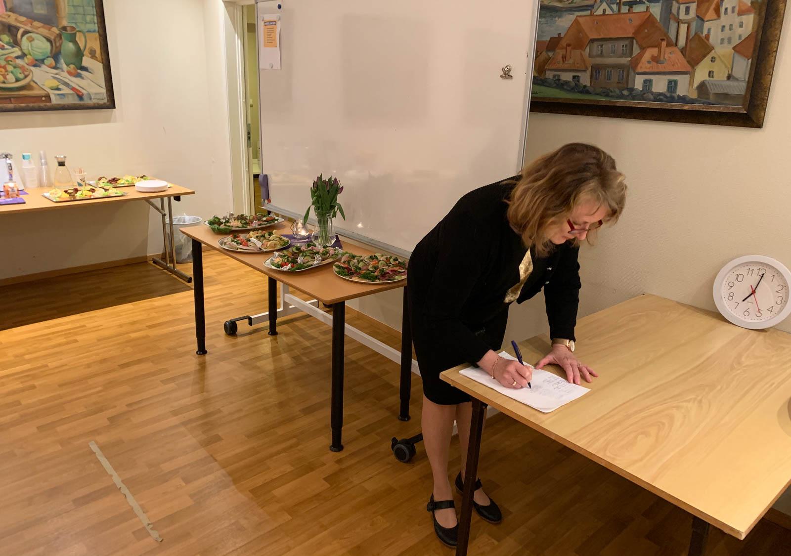 Gladys Aarstad noterer telefon nr. iht til covid-19 reglene.