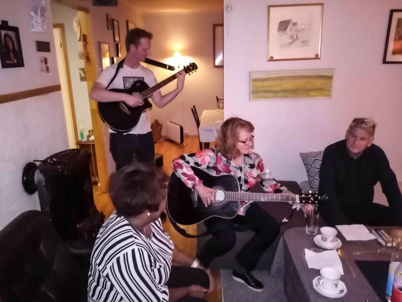 Dag øver på gitaren, mens Gladys varmer opp til lovsang.